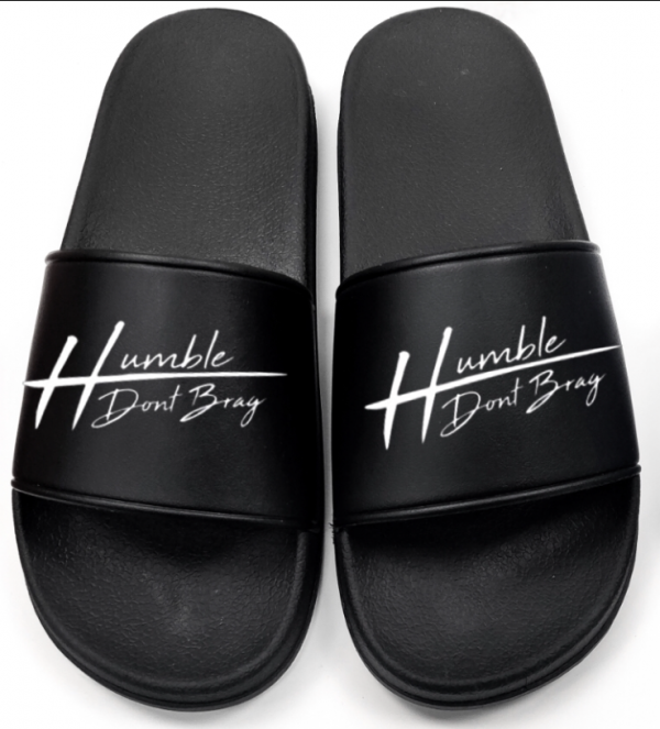 black slides with humble don't brag embossed on them